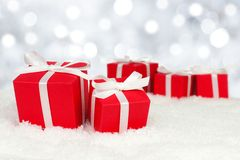 Gift boxes in snow with twinkling lights Stock Image