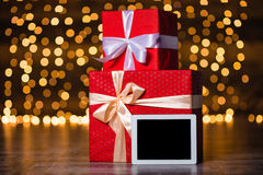 Gift boxes and tablet computer standing on the floor Royalty Free Stock Image