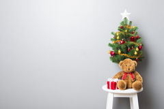 Gift boxes, teddy bear and small decorated Christmas tree on sto Stock Image