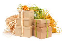 Gift boxes tied with natural raffia of different colors and top. Some gift boxes tied with natural raffia of different colors and topped with a flower on a white Stock Photos