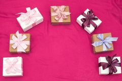 Gift boxes tied with satin coloured ribbon on a pink background. Royalty Free Stock Photo
