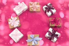 Gift boxes tied with satin coloured ribbon on a pink background. Royalty Free Stock Image