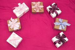 Gift boxes tied with satin coloured ribbon on a pink background. Stock Images