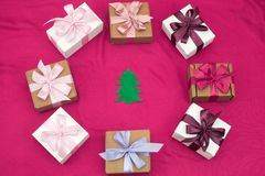 Gift boxes tied with satin coloured ribbon on a pink background. Stock Photography