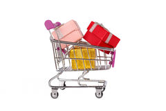 Gift Boxes in Trolley Shopping Card. Side view of shopping card or trolley with colorful gift boxes isolated on white background Royalty Free Stock Photography