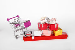 Gift Boxes in Trolley Shopping Card. Side view of shopping card or trolley with colorful gift boxes isolated on white background Royalty Free Stock Images