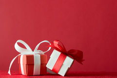 Gift boxes. Two gift boxes wrapped with ribbon on red background Royalty Free Stock Photos