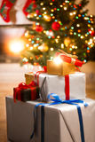 Gift boxes under Christmas tree next to fireplace at living room Stock Photo