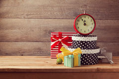Gift boxes and watch on wooden table. New Year celebration concept. Gift boxes and retro watch on wooden table. New Year celebration concept royalty free stock photo
