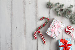 Gift boxes on white background. Christmas gift boxes with lollypop and candy canes under fur tree branch on white wooden background Stock Photo