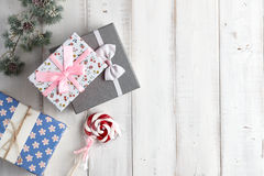 Gift boxes on white background. Christmas gift boxes and lollypop under fur tree branch on white wooden background Stock Photography
