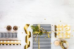 Gift boxes wrapped in black and white striped and golden dotted paper with, pine, cones, candle and wrapping materials on a white. Wood old background Royalty Free Stock Photo