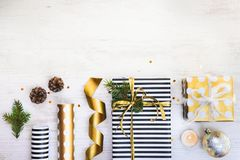 Gift boxes wrapped in black and white striped and golden dotted paper with, pine, cones, candle and wrapping materials on a white. Wood old background Royalty Free Stock Photography
