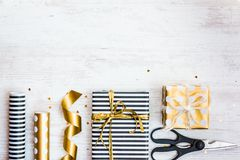 Gift boxes wrapped in black and white striped and golden dotted paper and wrapping materials on a white wood old background. Empty. Space Royalty Free Stock Images