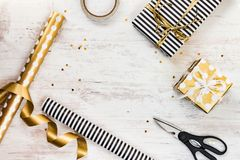 Gift boxes wrapped in black and white striped and golden dotted paper and wrapping materials on a white wood old background. Empty Stock Photo