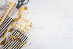 Gift boxes wrapped in black and white striped and golden dotted paper and wrapping materials on a white wood old background. Empty Royalty Free Stock Images