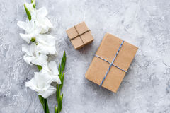 Gift boxes wrapped in craft paper near flower gladiolus on grey stone background top view copyspace Royalty Free Stock Photo