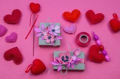 Gift boxes wrapped in red checked paper and the contents of a workspace composed. Different objects on a pink color table. Flat lay.Holiday decor concept stock photos