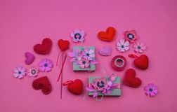 Gift boxes wrapped in red checked paper and the contents of a workspace composed. Different objects on a pink color table. Flat lay.Holiday decor concept stock photography