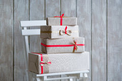 Gift boxes. Wrapped gift boxes with ribbons as Christmas presents on a chair Stock Photo