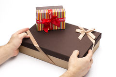 Gift boxes are wrapped up by tapes in hands on a white background. Cardboard box for gift packing Royalty Free Stock Image