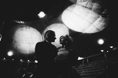 Gift brölloppardans i ett bakbelyst scenario Mjukt ögonblick av den första dansen Svartvit bild lyxigt arkivbild