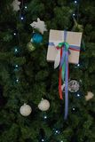 Gift on the branches of the Christmas tree stock photography