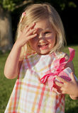 Gift Bright. Pretty little blond girl in sundress holding a pink birthday present outdoors and shielding eyes from sun Royalty Free Stock Photo