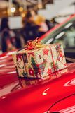 Gift in bright packaging lies on the hood of a red car royalty free stock image