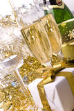 Gift, candle and champagne. Gift with golden bow, glasses of champagne and candle Stock Photo
