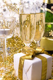 Gift, candle and champagne. Glasses of champagne gift with golden bow and candle Royalty Free Stock Photos
