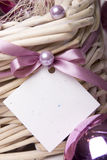 Gift card. Empty gift card tied with pink ribbon to a woven basket Royalty Free Stock Photography