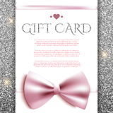 Gift card with bow on silver glitter background Stock Images