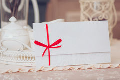 Gift card - closeup of a sign card. Gift card - closeup of a white card tied with a red ribbon Royalty Free Stock Photos