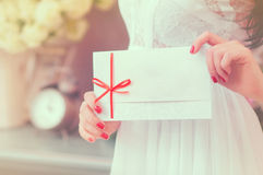 Gift card - closeup of woman showing sign card. Gift card - closeup of woman showing a white card tied with a red ribbon Stock Photos