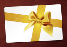 Gift card with golden ribbon bow Isolated on red Royalty Free Stock Photography