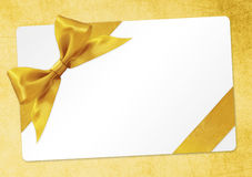 Gift card with golden ribbon bow Isolated on yellow Stock Photos