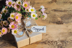Gift with a card with handwritten text and a bouquet of pink chr Stock Photos
