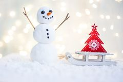 Gift card with a new year and christmas with a picture of a snowman with a sleigh against a backdrop of glowing garlands stock photo