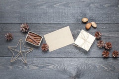 Gift, card, pine cones and cinnamonin on the dark table Royalty Free Stock Images