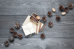 Gift, card, pine cones and cinnamonin on the table Stock Photo