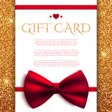 Gift card with red bow on golden glitter background Royalty Free Stock Images