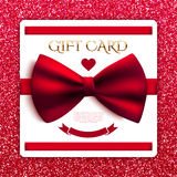 Gift card with red bow on red glitter background Royalty Free Stock Photography