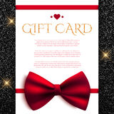 Gift card with red bow on shiny glitter background Stock Photography