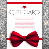 Gift card with red bow on silver glitter background Royalty Free Stock Photography