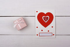 A gift and a card with red hearts on the table. Texture Royalty Free Stock Image