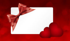Gift card with red ribbon bow and hearts  on red Stock Image