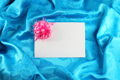 Gift card with ribbon. On blue satin Royalty Free Stock Image