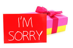Gift and card with the text I am sorry. A gift box of different colors tied with a purple ribbon and a red card with the text I am sorry written in it, on a Royalty Free Stock Image