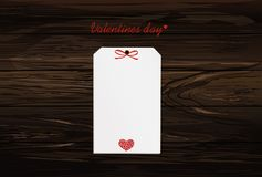 Gift card tied with a red heart. Vector. Valentine`s Day. On woo. Den background Greeting card for the holiday Stock Photos